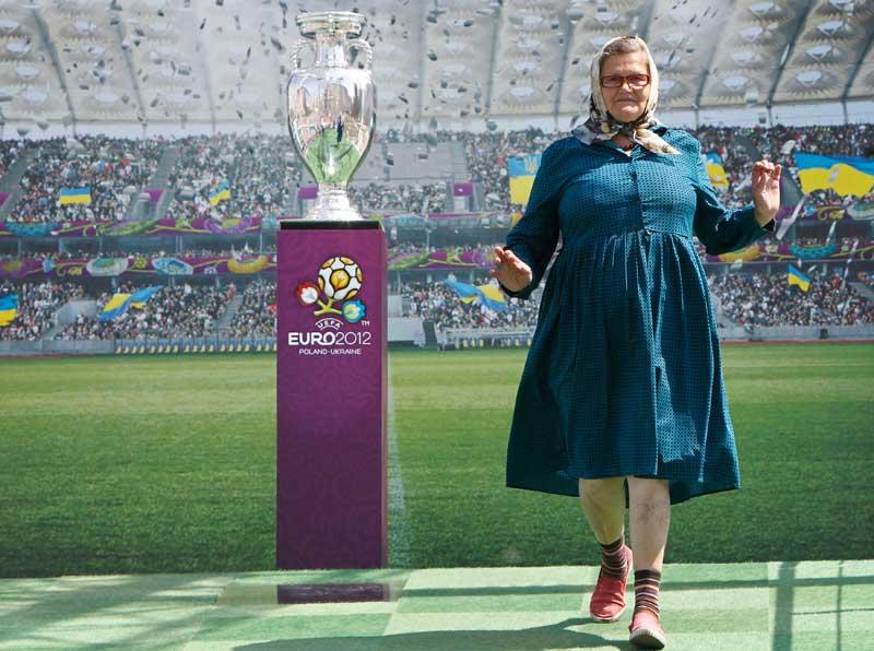 UCRÂNIA, 12.05.2012. Uma pose com orgulho junto ao troféu do Euro 2012 - que decorre na Ucrânia e Polónia a partir de Junho -, em exposição em Kiev.