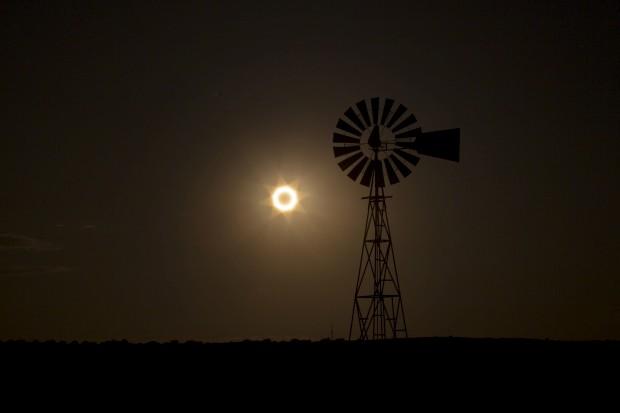 EUA, 21.05.2012. Um moinho de vento, em Albuquerque (Novo México), assiste à passagem da Lua entre o Sol e a Terra