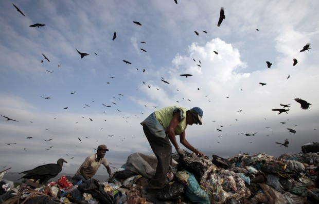 BRASIL, 31.05.2012. Um homem recolhe materiais recicláveis durante o último dia do Jardim Gramacho, no Rio. A maior lixeira brasileira a céu aberto foi encerrada após 36 anos de depósito de lixos.