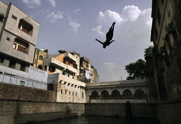 ÍNDIA, 01.06.2012. Um rapaz mergulha nas águas interiores do santuário do Sufi (Santo) Nizamuddin Auliya, em Nova Deli. As temperaturas atingiram 45 graus.