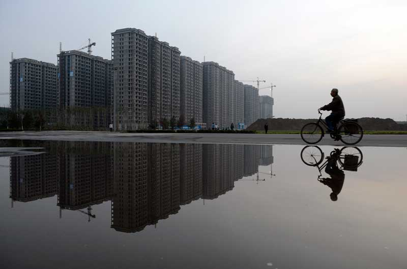 CHINA, 04.06.2012. A pedalar junto de um complexo residencial em construção. Em Taiyuan.