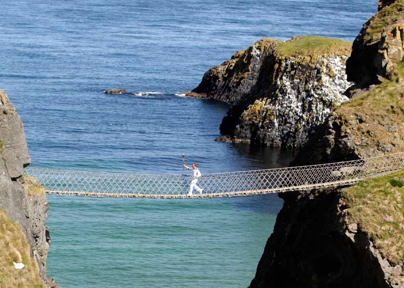 IRLANDA DO NORTE, 06.06.2012. A tocha olímpica transportada por Denis Broderick na ponte de cordas de  Carrick-a-Rede, perto de Ballintoy. A tocha segue rumo a Londres.