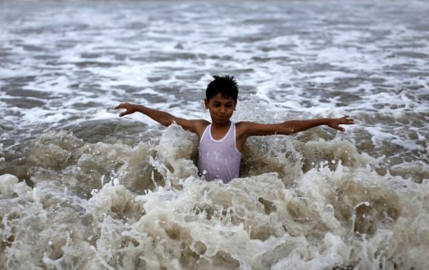 ÍNDIA, 06.06.2012. Um rapaz brinca nas águas do Mar Arábico durante uma chuva de pré-monção em Mumbai