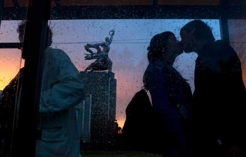 RÚSSIA, 07.06.2012. Um casal beija-se numa estação de comboios em frente de uma estátua da era soviética (que representa um homem, com um martelo, e uma mulher, com uma foice), em Moscovo.