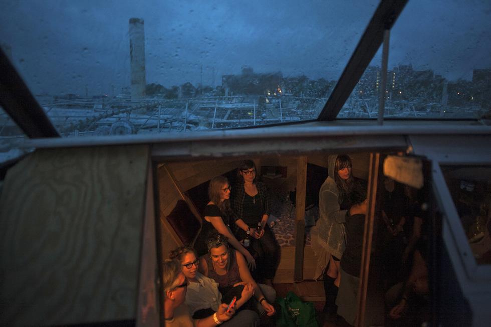 Os hóspedes aproveitam a chuva para se refugiarem no interior de um dos barcos
