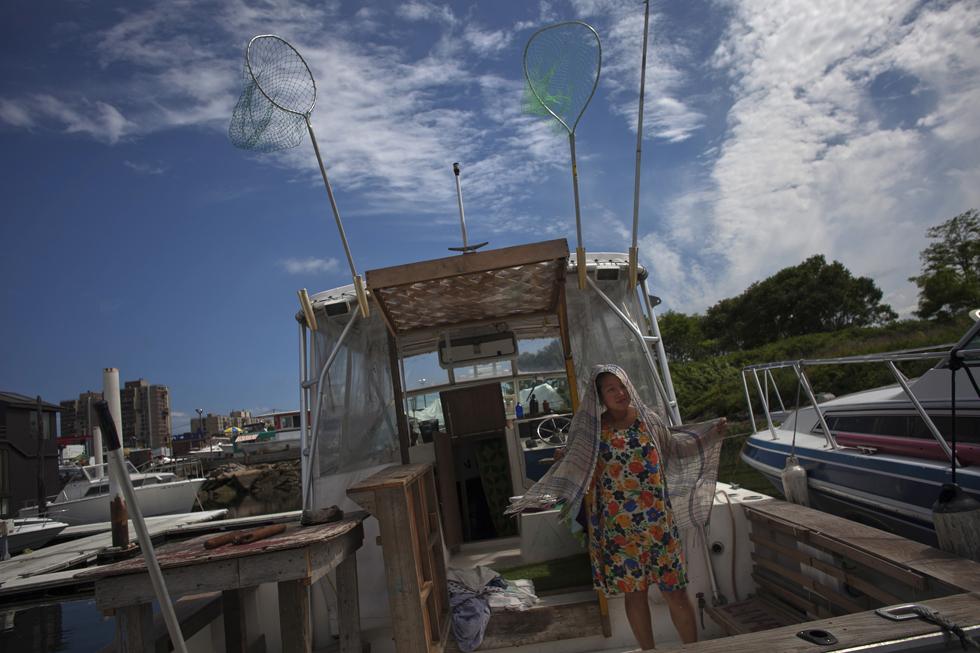 A artista Angie Kang prepara um dos barcos