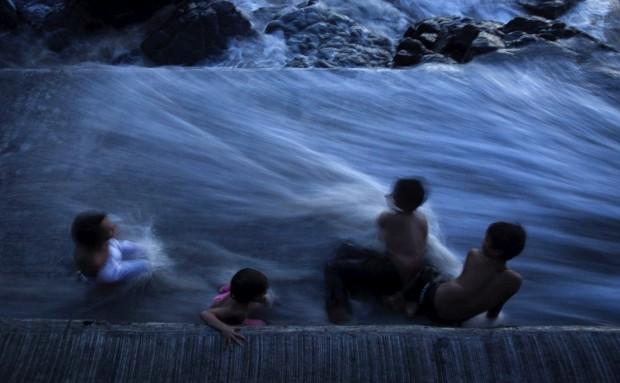 ÍNDIA, 13.06.2012. Crianças brincam enquanto a água corre pelas escadarias do santuário Haji Ali, em Mumbai