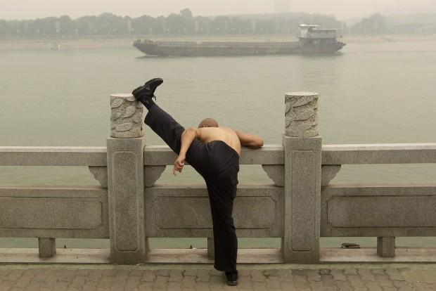 CHINA, 15.06.2012. Um homem exercita-se na margem do rio Han enquanto um navio desliza por entre a névoa. Em Wuhan