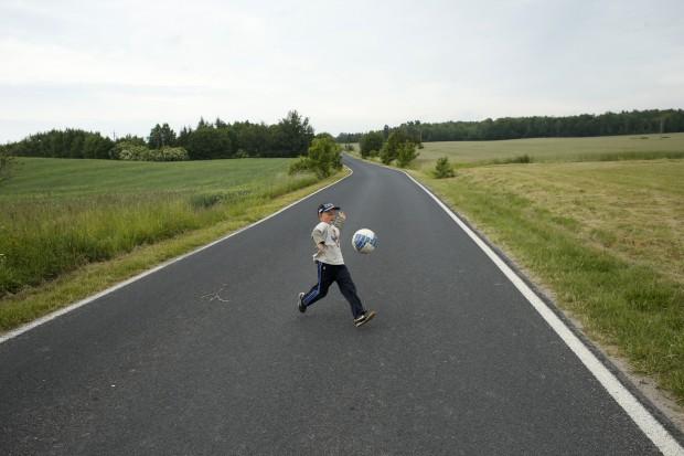 POLÓNIA, 16.06.2012. Outro futebol: um rapaz brinca com a sua bola numa estrada em Lisewo, aldeia perto de Gniewino, onde a selecção espanhola tem o seu campo de treino
