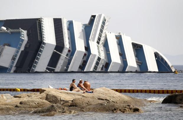 ITÁLIA, 20.06.2012. Veraneantes na ilha de Giglio com o afundado cruzeiro Costa Concórdia (ainda) no horizonte
