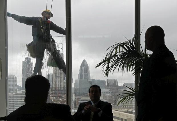 Visto do interior do Shard: uma reunião enquanto um trabalhador limpa janelas