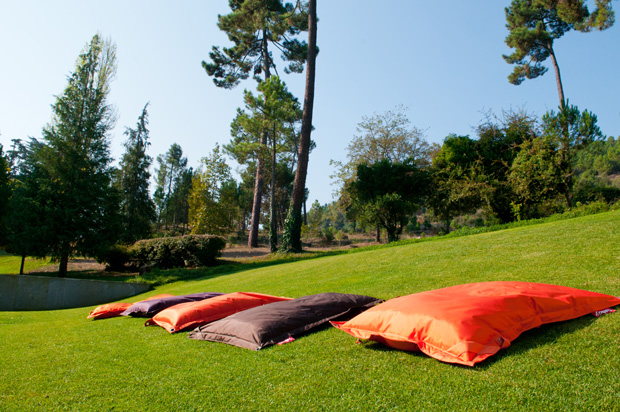 Almofadas que rodeiam a piscina exterior e convidam a relaxar ao sol