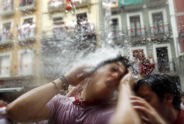 ESPANHA, 06.07.2012. Da varanda veio a água e estes participantes das festas de San Fermín, em Pamplona, apreciaram este tradicional momento de frescura