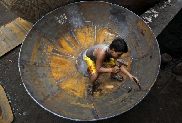 ÍNDIA, 12.07.2012. Um jovem trabalhador numa fábrica de utensílios de ferro, em Calcutá