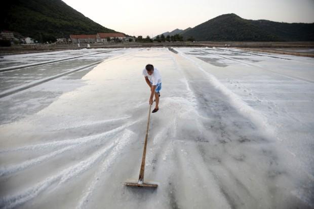 CROÁCIA, 31.07.2012. Um trabalhador recolhe sal numa salina de Ston, no sul da Croácia