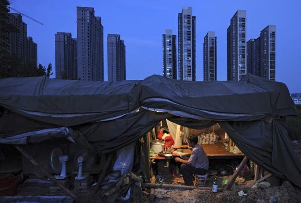 CHINA, 02.08.2012. Um trabalhador janta na sua barraca no local de construção de um complexo residencial dem Hefei.