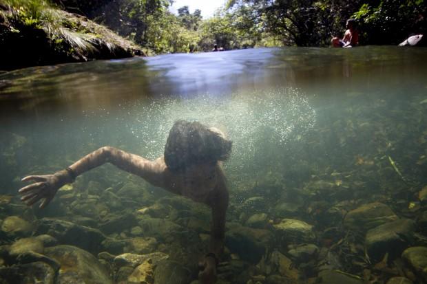 BRASIL, 25.07.2012. Uma criança de uma tribo indígena nada no rio de São Miguel, durante o XII Encontro de Culturas Tradicionais da Chapada dos Veadeiros