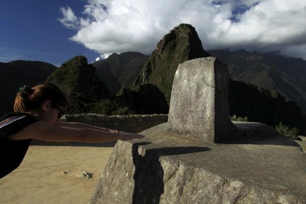 Uma mulher coloca as mãos no relógio solar inca, o Intihuatana