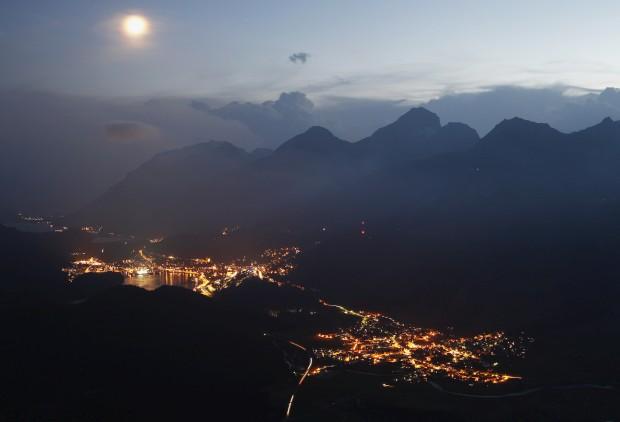 SUÍÇA, 23.08.2012. A estância de esqui St. Moritz e a vila de Celerina vistos à noite a partir das montanhas de Muottas Muragl