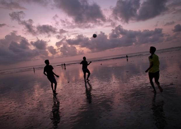ÍNDIA, 23.08.2012. Jogo de futebol na praia de Juhu, Mumbai sob as nuves da monção