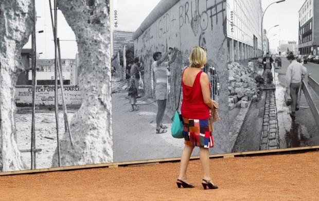 ALEMANHA, 25.08.2012. Uma mulher observa imagens históricas numa exposição perto do Checkpoint Charlie, a antiga passagem de fronteira nos tempos do Muro de Berlim