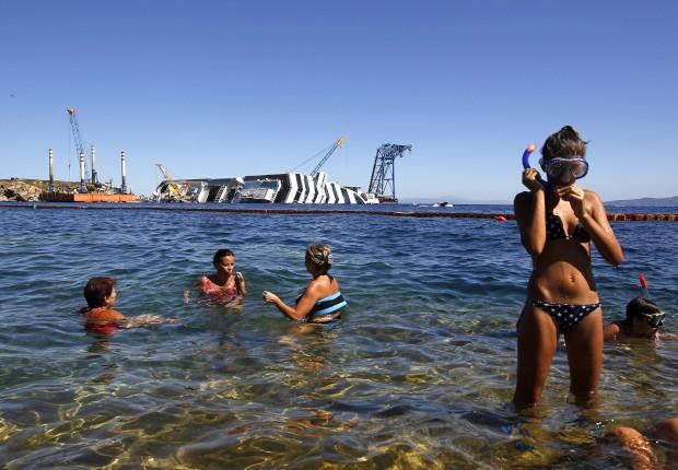 ITÁLIA, 28.08.2012. Turistas perto do porto de Giglio com o naufragado Costa Concordia no horizonte: já se tornou atracção turística, com direito a passeios de barco para vê-lo de perto ou actividades de mergulho