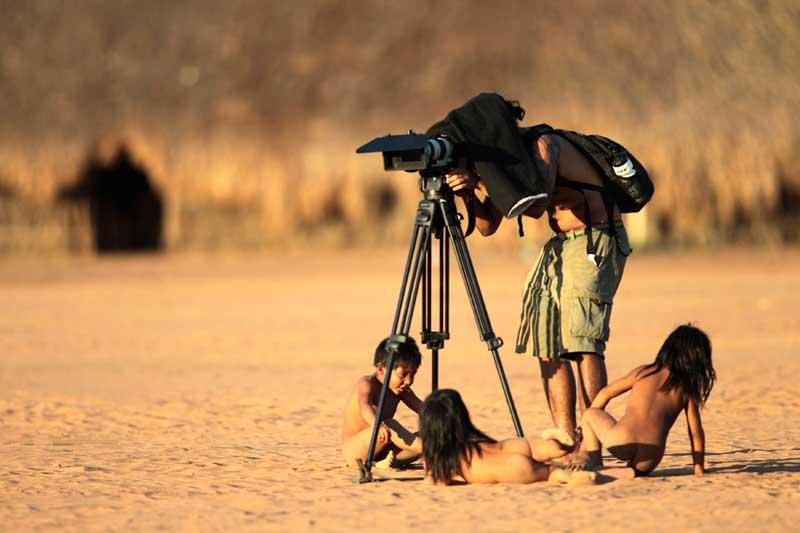 BRASIL, 17.08.2012. Crianças da tribo Yawalapiti brincam em redor de um fotógrafo durante o Qirup, ritual de homenagem a personalidades falecidas, no Parque Nacional de Xingu