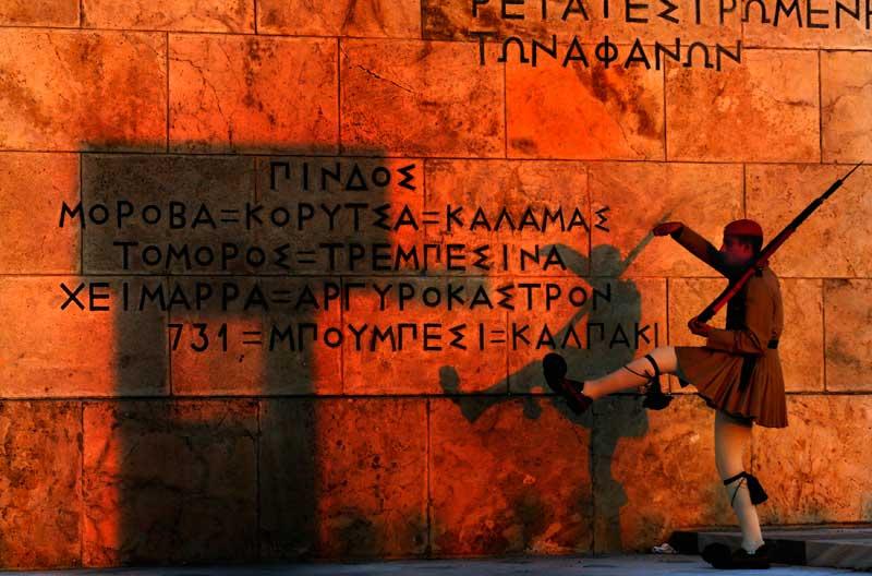 GRÉCIA, 04.09.2012. Um guarda presidencial marcha em frente do Memorial ao Soldado Desconhecido em frente do parlamento ao pôr-do-sol em Atenas.