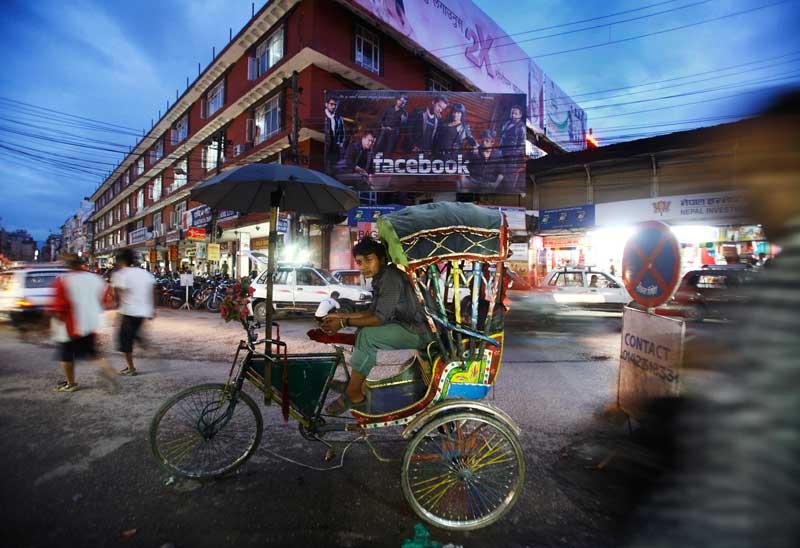 NEPAL, 10.09.2012. O condutor de um rickshaw espera passageiros numa rua de Kathmandu.
