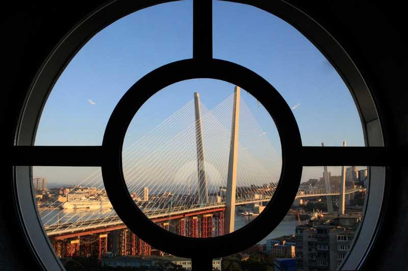 RÚSSIA, 10.09.2012. A nova ponte de Vladivostok, sobre a baía, vista de uma janela vizinha.