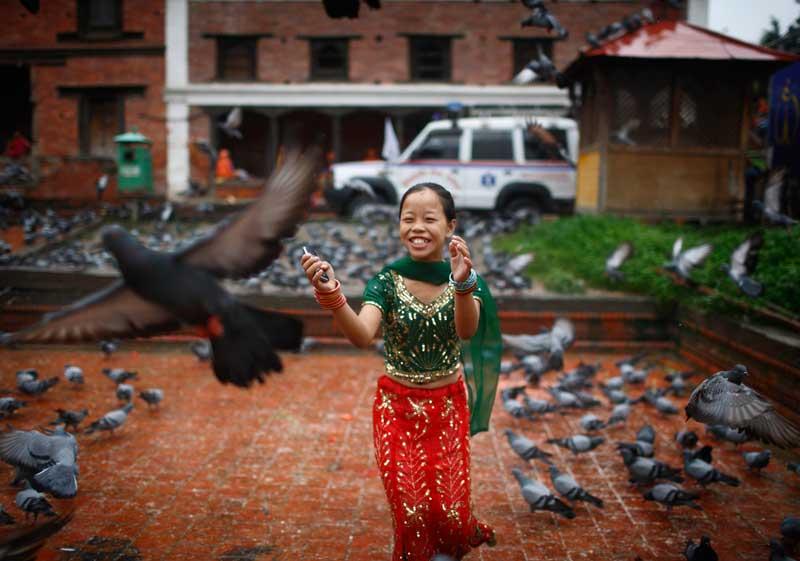 NEPAL, 18/09/2012. A brincar com os pombos do templo Pashupatinath durante um festival (Teej), em Kathmandu