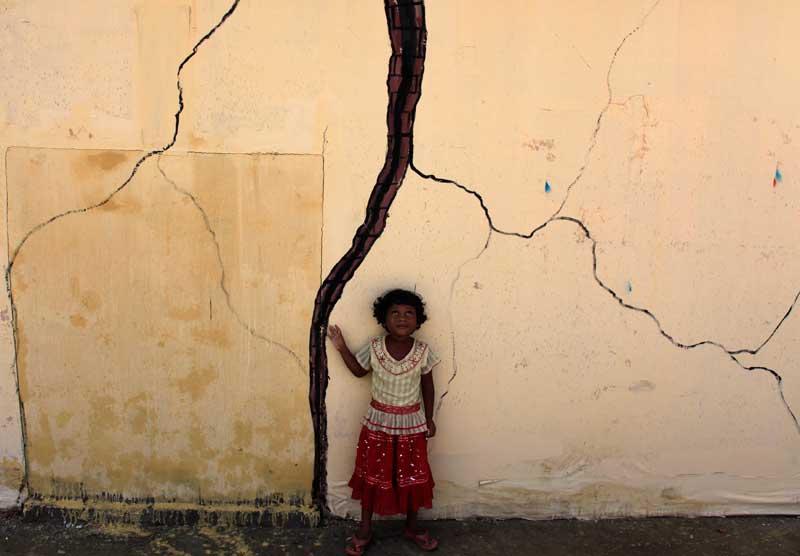 BANGLADESH, 19/09/2012. Na parte antiga de Daca, a capital, uma rapariga observa treinos do exército e bombeiros. As aparências enganam: as rachas na parede são falsas e fazem parte do exercício