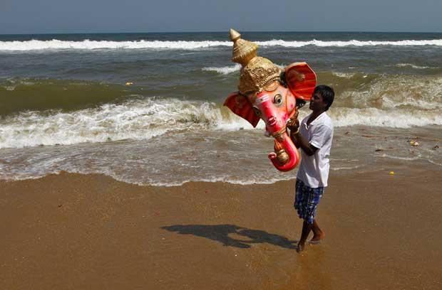 ÍNDIA, 23/09/2012. Um devoto transporta uma estátua do deus hindu Ganesh, depois de mergulhá-lo na baía de Bengali, durante o festival dedicado a Ganesh em Chennai (antes Madras)