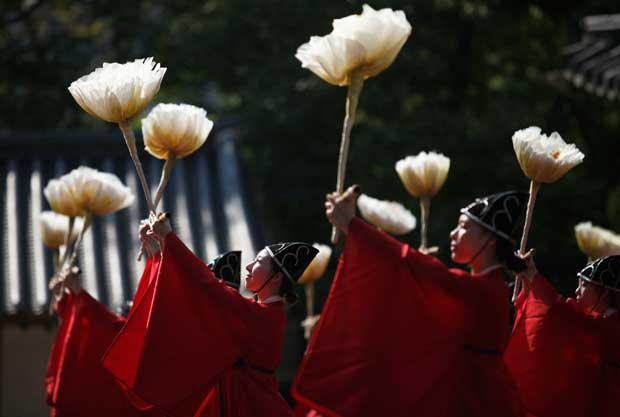 COREIA DO SUL, 24/09/2012. Estudantes universitários, licenciados em dança tradicional coreana, em trajes tradicionais durante uma cerimónia num templo da Universidade Sungkyunkwan em Seul