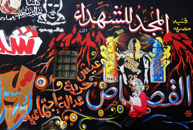 EGIPTO, 26.09.2012. Uma mulher passa por uma parede de grafitis no Cairo, perto da praça Tahrir