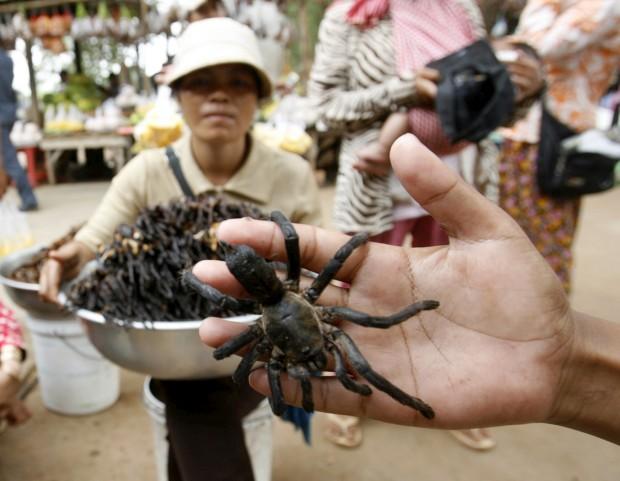 Um vendedor de aranhas fritas posa com as suas especialidades enquanto aguarda clientes na estação de   autocarros de Skun, Camboja. Dez aranhas estaladiças fritas em alho custam cerca de 2€. Diz-se que até têm  um certo sabor a