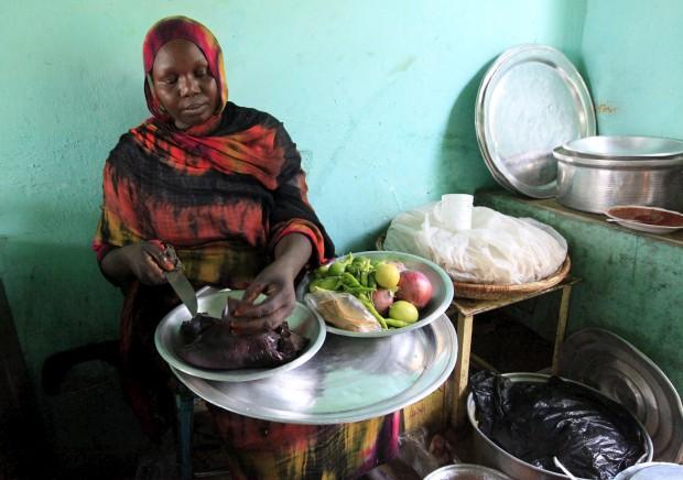 Uma mulher prepara um prato feito de carne de camelo na sua loja de Tamboal, Al Jazeera, Sudão
