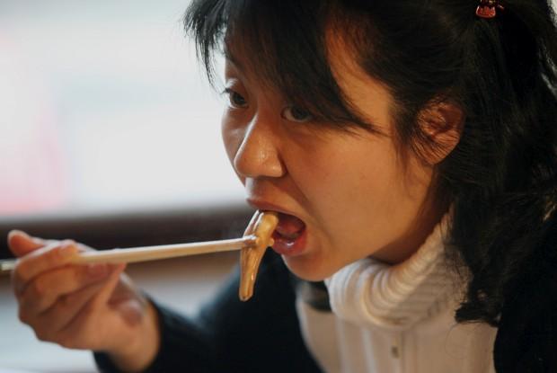 Uma cliente chinesa come, em Pequim, um prato realmente radical: chama-se algo como