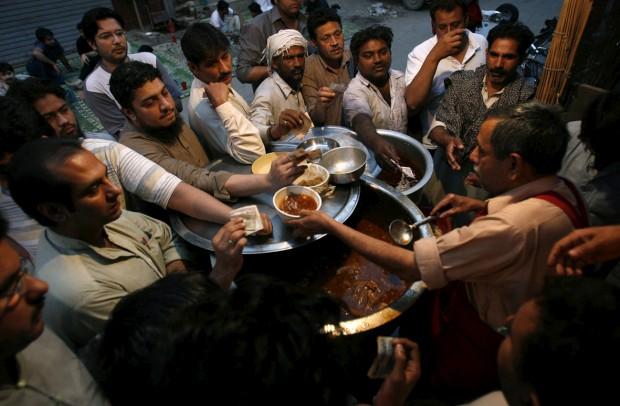 À espera de uma tigela de siri paya, prato tradicional para o pequeno-almoço feito a partir de cabeças e patas de cabra. Em Lahore, Paquistão