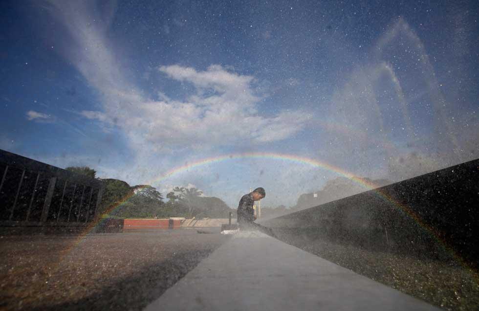 BIRMÂNIA/MYANMAR, 7.10.2012. Água e arco-íris num parque de Yangon