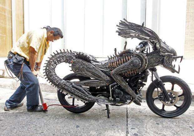 Na Tailândia. O artista Roongrojna Sangwongprisarn criou uma motocicleta de formas alienígenas a partir de materiais reciclados e partes de carros e bicicletas