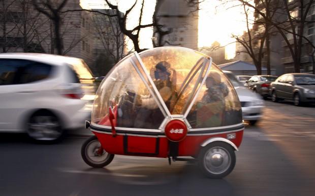 Um normalíssimo carro-cápsula eléctrico na China, conduzido aqui por uma mulher, com o filho ao lado, por Pequim.