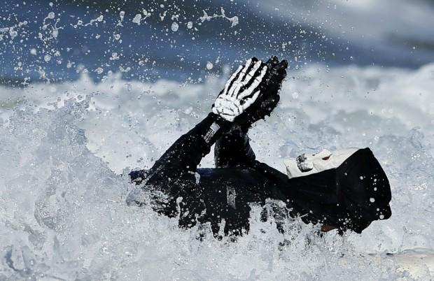 EUA, 27.10.2012. Um homem, vestido de esqueleto, surfa de costas durante um concurso de surf sob o mote do Halloween em Santa Monica