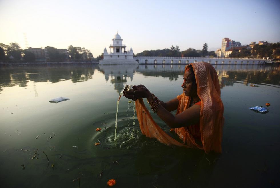 Nepal, 20.11.2012. Uma devota em oração ao nascer do Sol durante o festival Chhat em Katmandu