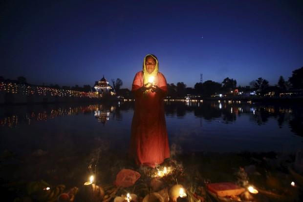 Uma devota aguarda o nascer do Sol, em Katmandu