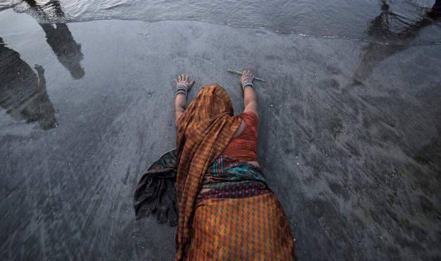 Uma devota deita-se no areal junto ao mar Arábico, em Mumbai