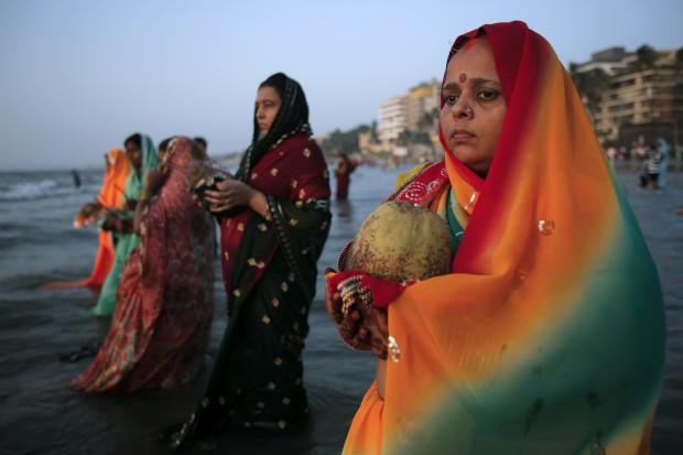 Uma devota reza enquanto se banha no mar Arábico, em Mumbai