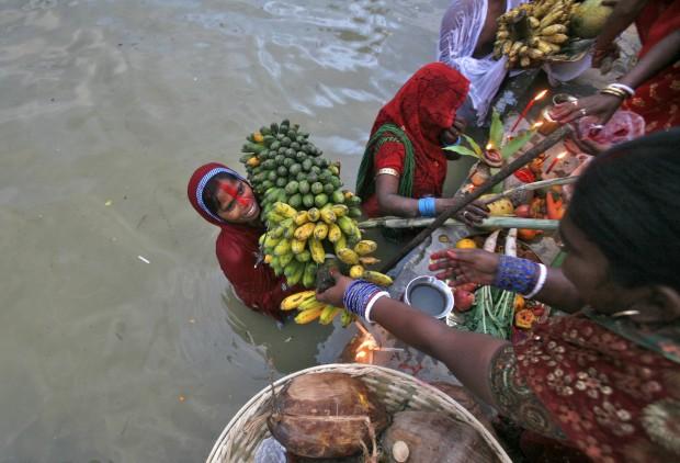 Uma devota segura uma cesta de bananas nas águas do lago Durga Dari, nos arredores de Agartala, Índia