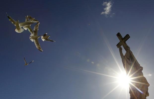 Voo de gaivotas sobre a estátua do Anjo, de Ferrata, na ponte de Sant'Angelo