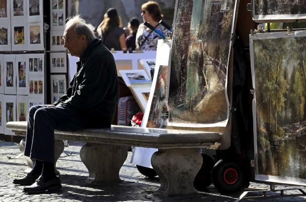 Rodeado de arte, um homem descansa na piazza Navona